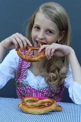 Young girl bites pretzel  in Oktoberfest