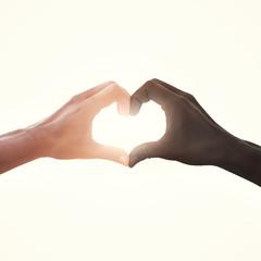 interracial couple in love heart shape hand gesture