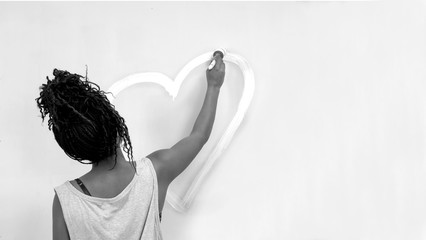 girl painting a heart on the wall, african girl