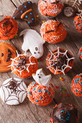 Halloween cupcakes and gingerbread cookies close-up. vertical top view