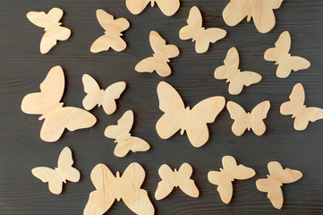 wooden silhouettes of butterflies on a black background