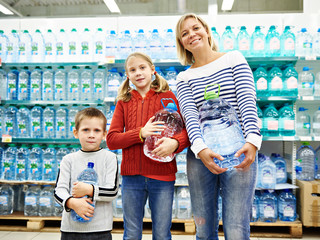 Woman with children is holding bottle drinking water in shop