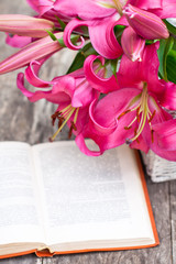 White basket with pink lily flowers bouquet and old book on rust