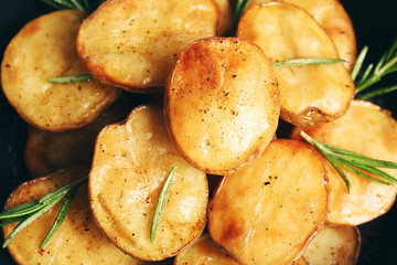 Delicious baked potato with rosemary in frying pan close up