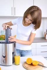 Young beautiful woman using juicer, preparing orange juice