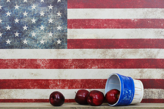 Basket of red apples by vintage American flag canvas background