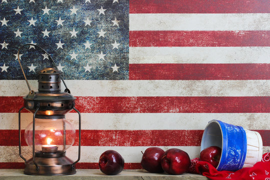 Basket of red apples and antique lantern by vintage American flag background