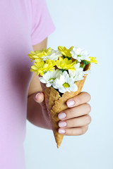 Woman holding flowers in waffle cones, close up