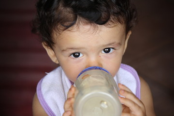 Little girl drinks milk from a bottle