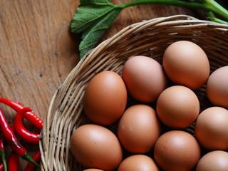 basket eggs and vegetable on vintage wooden background