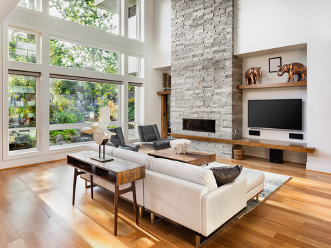 Beautiful living room with hardwood floors, fireplace, and large bank of windows with view of lush vegetation, in new luxury home
