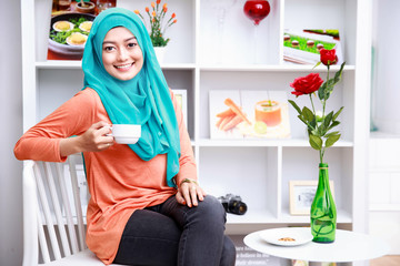 attractive muslim woman enjoying a cup of tea at decorated livin