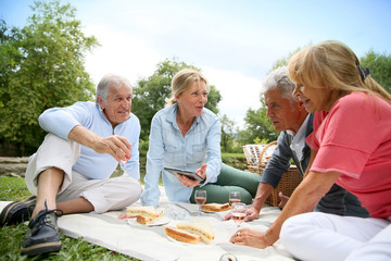 Foto auf AluDibond Picknick Group of senior people enjoying picnic on sunny day