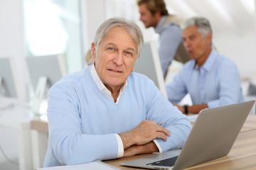 Portrait of senior man working on laptop, training class