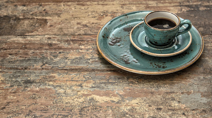 Blue cup of black coffee on wooden background. Vintage style