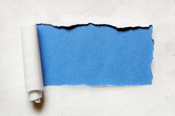 Tearing a paper frame hole with blue background