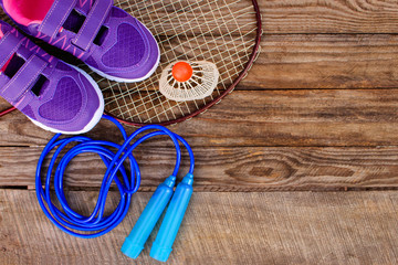 Sports equipment: the birdie is on the racket, skipping rope and sneakers on wooden background