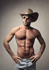 Handsome man posing with a cowboy hat