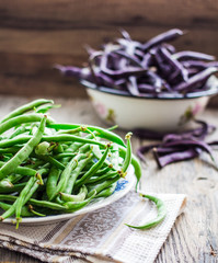 raw purple and green beans on a gray wooden table, clean eating