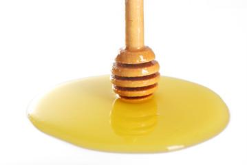 Wooden dipper in honey on light background