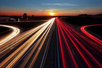 Speed Traffic light trails on highway at sundown time, long