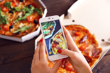 Woman taking a photo of pizza with the smartphone
