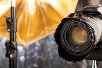 Digitale Spiegelreflexkamera mit Objektiv und Studioleuchte mit goldenem Schirmreflektor