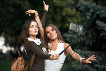 Girlfriends taking picture with smartphone on selfie stick