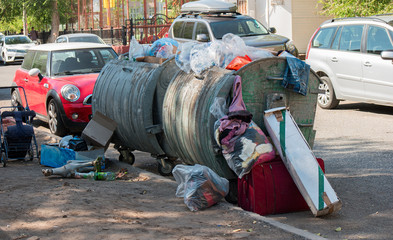 Garbage overfilled trash dumpsters in the street, surrounded by