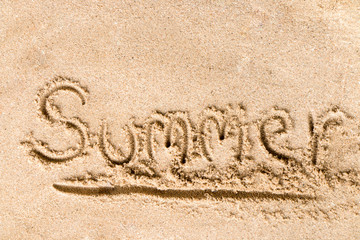 Summer text write on sand at the beach, Summer concept.