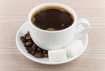 Cup of hot coffee, coffee beans and pieces of sugar