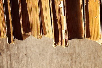 Pile of old books. A number of old books on a wooden surface close up