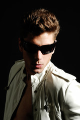 Young handsome man wearing dark sunglasses on black background