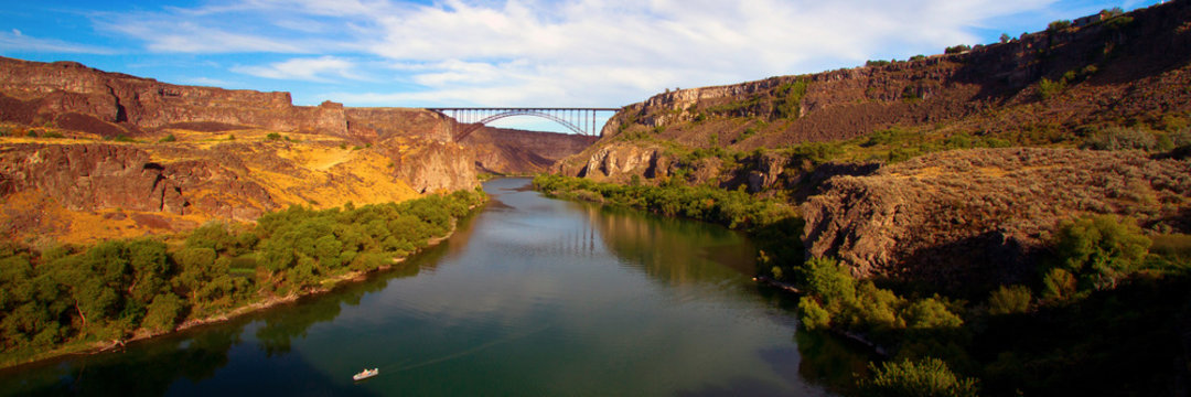 Wide panorama of golden evening light on I. B. Perrine Bridge and the Snake River at Twin Falls, Idaho