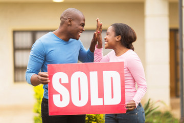 young african couple celebrating their house been sold