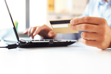 Close Up Of A Man Shopping Online Using Laptop With Credit Card
