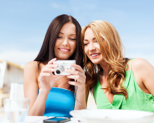 girls with camera in cafe on the beach