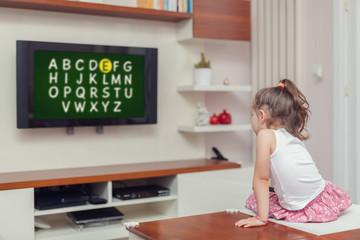 cute little girl learning alphabet on tv