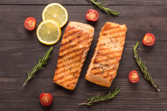 Grilled salmon and tomato, lemon, rosemary on the wooden backgro