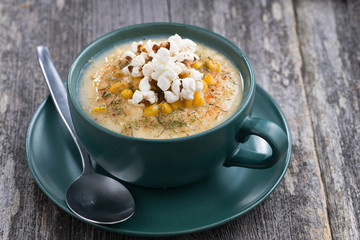 corn soup with popcorn in ceramic cup on wooden table