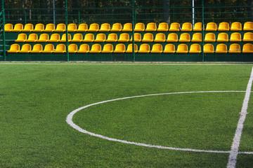 Green grass and yellow seats at empty mini soccer stadium