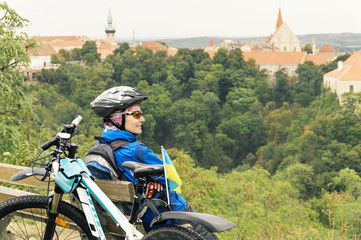Woman cyclist enjoy the view of the Medieval Czech town.