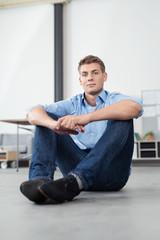 junger mann sitzt auf dem fußboden in einem modernen apartment