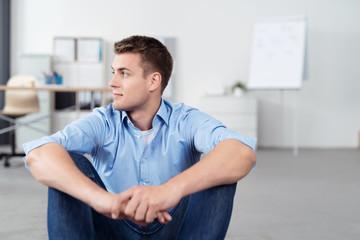 nachdenklicher junger mann sitzt im büro auf dem fußboden
