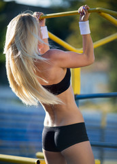 Sexy seductive woman doing pull-up on the horizontal gym bar