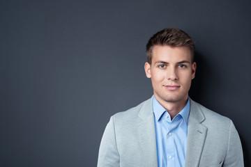lächelnder junger mann vor grauem hintergrund