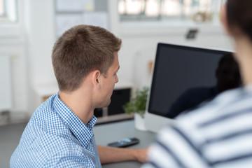 kollegen schauen gemeinsam auf computer