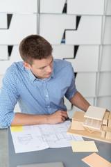 architekt arbeitet an einem haus-modell