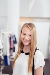 junge lächelnde frau in einer boutique