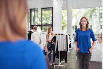 frau probiert ein blaues shirt an und betrachtet sich im spiegel